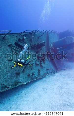 A solitary diver is swimming alongside the wreck of the Tibbetts, a sunken warship off of Cayman Brac. The deck guns can be seen in the background. - stock photo