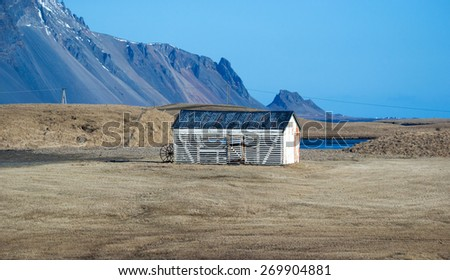 A solitary farm house stands on the vast grass fields in a farm in Stokksness, on the southern coast of Iceland. - stock photo