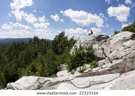 A solitary figure sits atop a stone outcrop atop a mountain in the midst of the Vermont wilderness. - stock photo