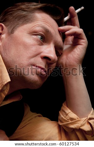 A solitary man sits at a bar and smokes a cigarette - stock photo