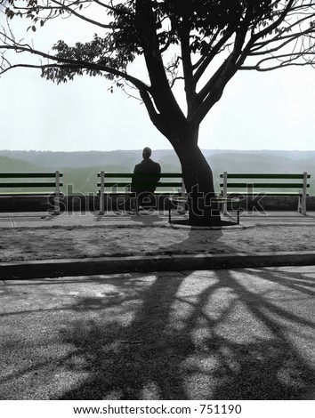 A solitary man watches the setting sun from a city park - stock photo