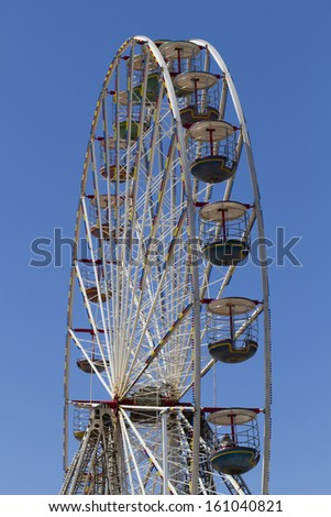 A solitary person on a Ferris Wheel against a blue sky