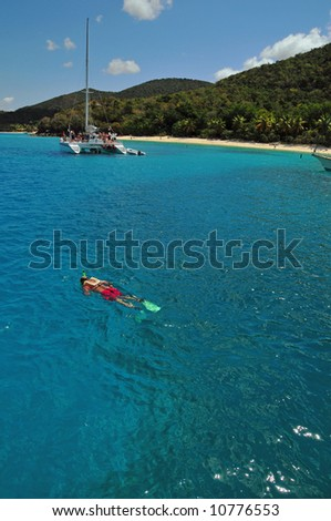 A solitary snorkeler snorkels off a remote tropical island - stock photo
