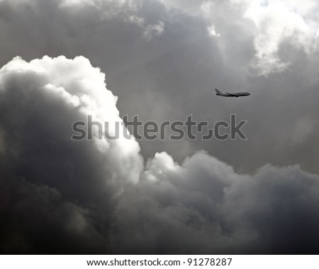 A solitary transport airplane flying high above a huge dramatic cloud in inclement weather. - stock photo