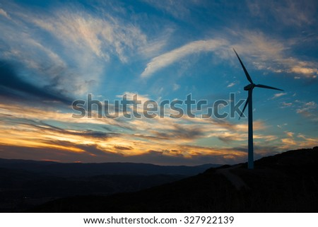 A solitary Wind Turbine silhouetted against a dramatic sunset sky. Landscape Format - stock photo