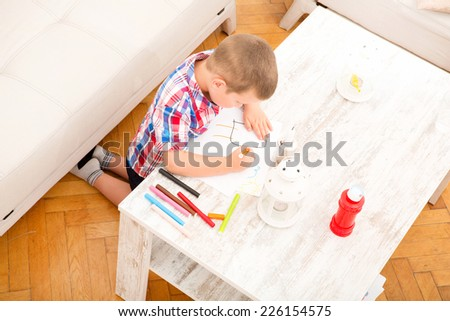 A son drawing at the table at home.  - stock photo
