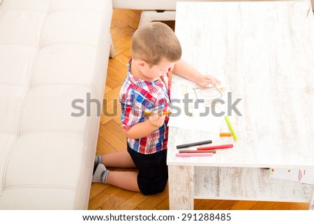 A son drawing at the table at home.