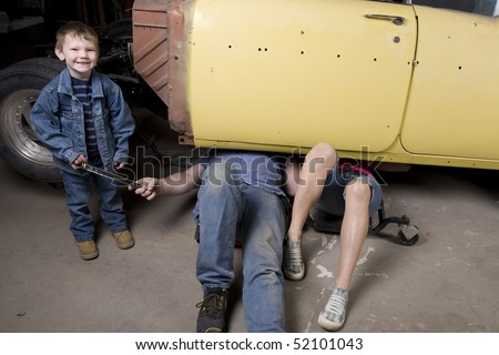 A son handing his father a tool while he and his wife are under the car working.
