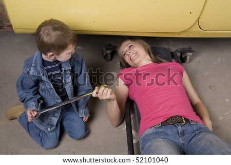 A son handing his mom a wrench to help her fix the car with happy expressions on her face. - stock photo