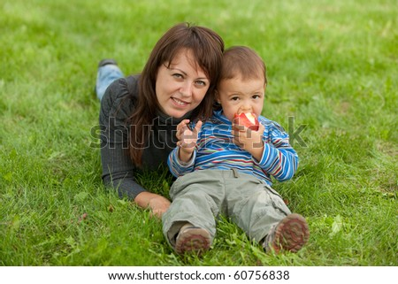 A son is eating a red apple sitting at his mother on the green grass