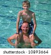A son sits on his Dad's shoulders at the pool - stock photo