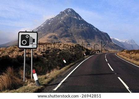 A sopped camera warning sign by the roadside near Glencoe, Scotland - stock photo