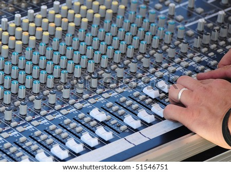 A sound mixing board in use. - stock photo