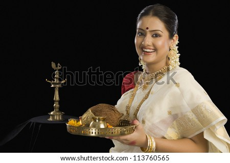 A South Indian woman holding a plate of religious offerings - stock photo
