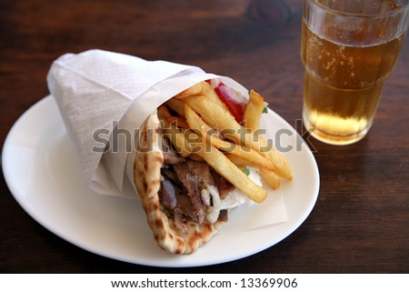 A souvlaki pitta gyros, the standard Greek kebab or meat wrap, with fries, yoghourt and salad, and a beer. - stock photo