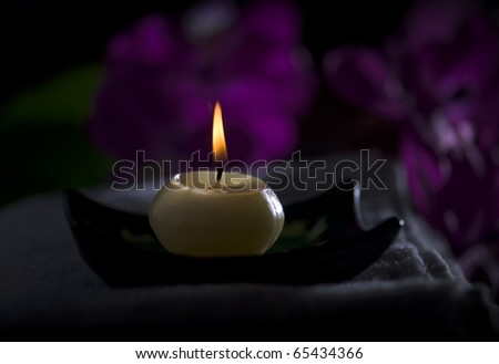 A spa candle on a towel/dark settings - stock photo