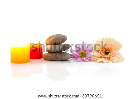 A spa theme still life with candle, river stones and flowers, isolated on white with reflections - stock photo
