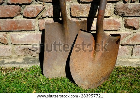 A spade and shovel are a rusty pair of hand digging implements. - stock photo