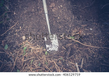 A spade in a hole outside - stock photo