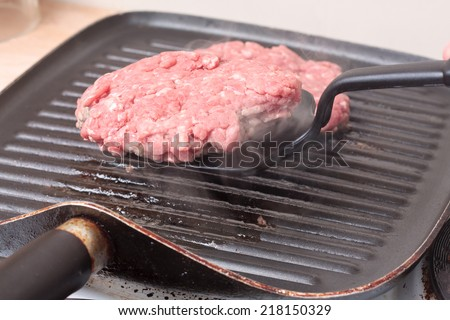A spatula is used to flip over a burger patty cooking on a grill-pan - stock photo