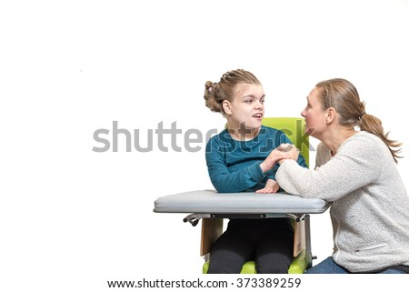 A special needs child in a wheelchair relaxing with a carer / Working together with disability