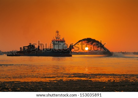 A spectacular take on a dredging ship in action at Palm Jumeirah, as the golden sun sets in Dubai - stock photo