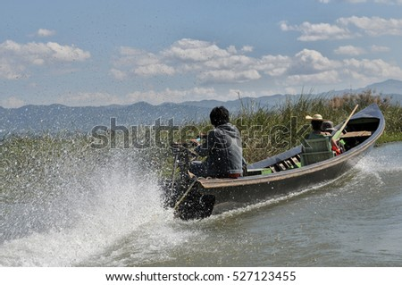 A speed boat with lots of water in the air behind the engine transporting a female passenger at the Inle Lake in Myanmar with blue sky in the background