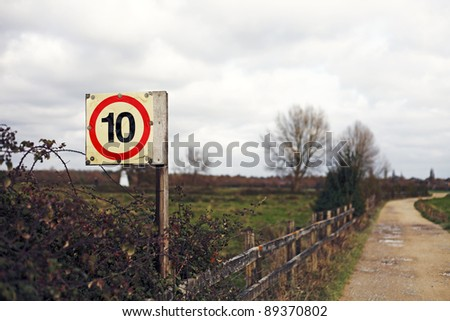 A speed limit sign on a rural countryside dirt road against a dramatic stormy sky. - stock photo