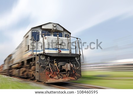 A speeding diesel powered train zooming on a railway track against a blue cloudy sky. - stock photo