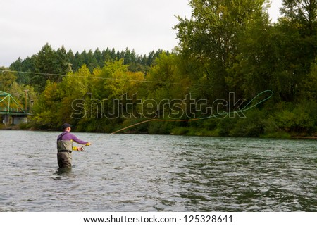 A spey casting fly fisherman swings flies for steelhead on the Willamette River in Oregon. - stock photo