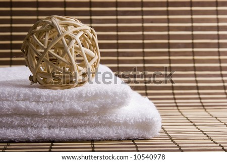 A sphere on two white towels on a bamboo mat - stock photo