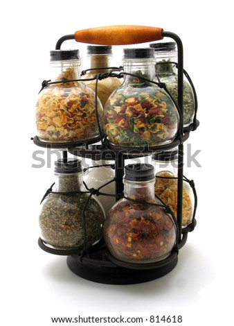 A spice rack filled with bulbs of various herbs - stock photo