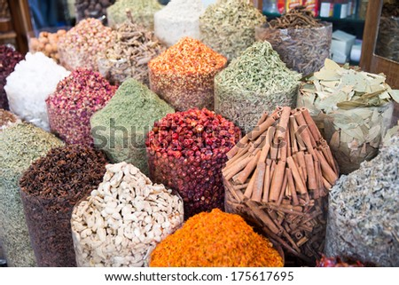 A spice vendor's display at a local market in Dubai: colorful, powdered spices in large sacks - stock photo