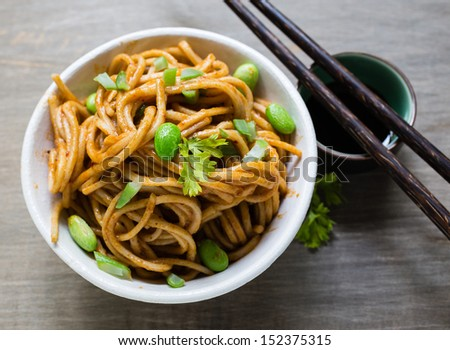 A spicy Asian noodle dish with chopsticks. - stock photo
