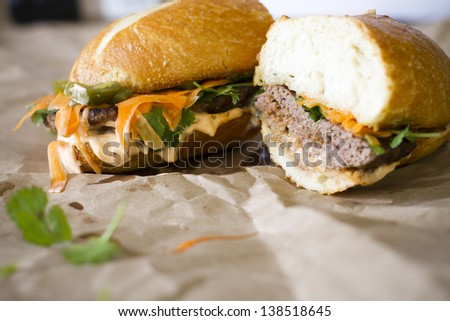 A spicy lamb bahn-mi burger with cilantro, spicy aoli, jalepenos, and pickled carrots. - stock photo