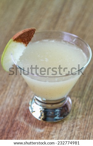 A spicy pear cocktail isolated on a wooden table
