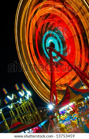 A spinning ferris wheel, colorful flags and carnival games at night - stock photo