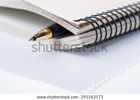 A spiral notebook with black ball pen on the white table, isolated