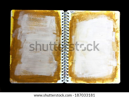 A spiral notebook with layers of acrylic paint over obscured text lines, against a black background - stock photo