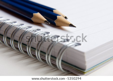 A spiral ring bound pad and three pencils
