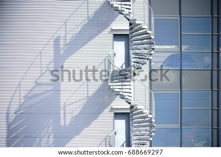 A Spiral Staircase, Fire Escape On The Side Of A Industrial Building Facade  / Spiral