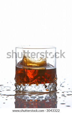 A splash into a whiskey glass reflected on white background