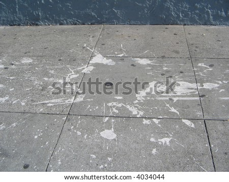 a splash of spilled paint has left and abstract painting on the cement sidewalk
