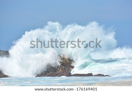 A splashing big wave crashing into the rocks in the rough wild water of the Indian Ocean on a stormy sunny day during springtime in South Africa. - stock photo