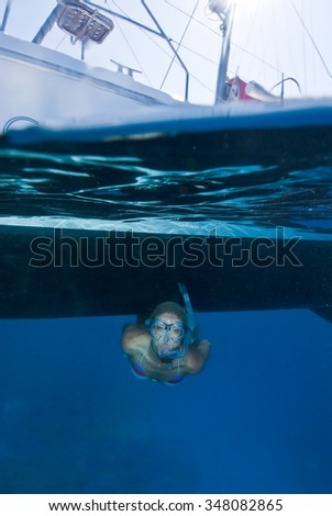 A split level photograph of a female freediver in clear blue water - stock photo