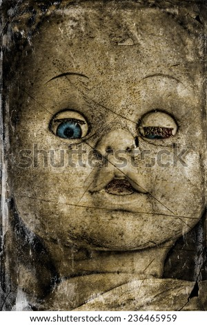 A spooky and disturbing image of a doll on a grunge and old photo effect.  - stock photo
