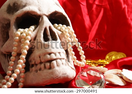 A spooky skull thats holding on to some treasure.                - stock photo