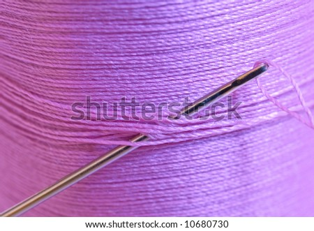 A spool of magenta thread and a needle