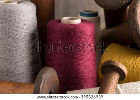 A spool of maroon thread in the center along side other color spools of thread and empty wooden spools. - stock photo
