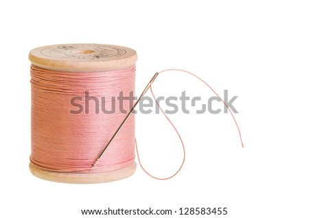 A spool of pink sewing thread with a needle on white - stock photo